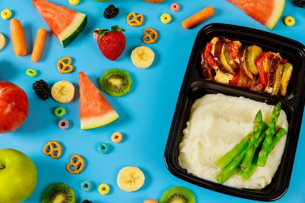 Lancheiras com purê de batatas e legumes prontos para o trabalho ou escola Foto Premium