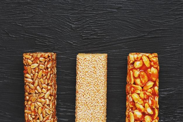 Lanches saudáveis. comida de dieta de aptidão. barra de grãos com amendoim, gergelim e sementes em uma placa de corte sobre uma mesa escura, barras de energia Foto Premium