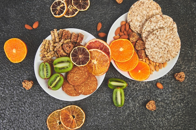 Lanches saudáveis - variedade de barra de granola de aveia, batatas fritas de arroz, amêndoa, kiwi, laranja seca Foto Premium