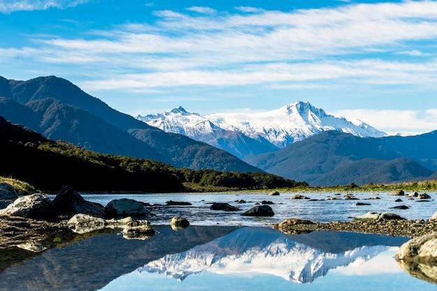 Landscpae impressionante do reflexo da montanha de neve no rio. céu azul e um pouco nublado. Foto Premium