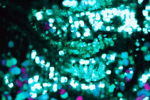 Lantejoulas verdes borradas no fundo Foto gratuita