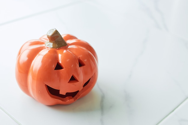 Lanterna de jack cabeça de abóbora de halloween no piso de mármore branco Foto Premium
