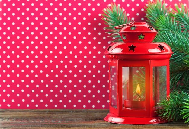 Lanterna de vela vermelha de natal e árvore de natal em fundo de bolinhas vermelhas. Foto Premium