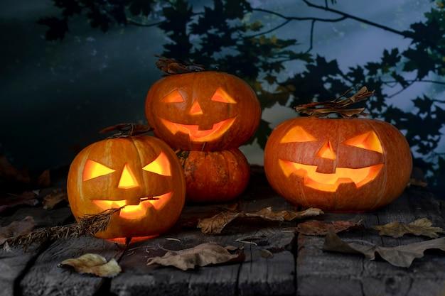 Lanterna principal do jaque o de três abóboras de halloween na tabela de madeira em uma floresta místico na noite. projeto do dia das bruxas Foto Premium