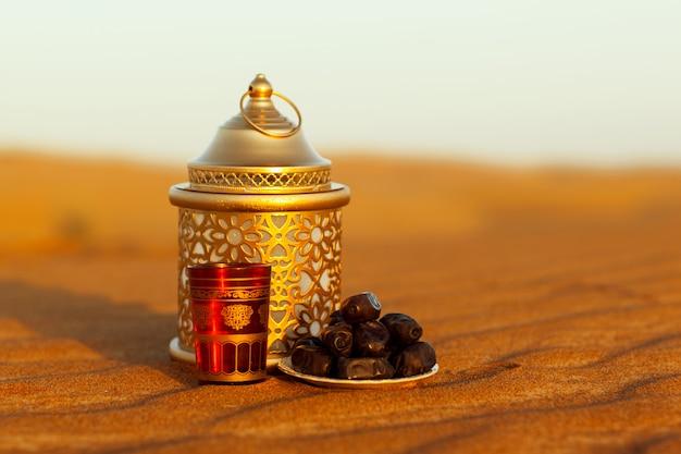 Lanterna, taça e datas estão na areia no deserto Foto Premium