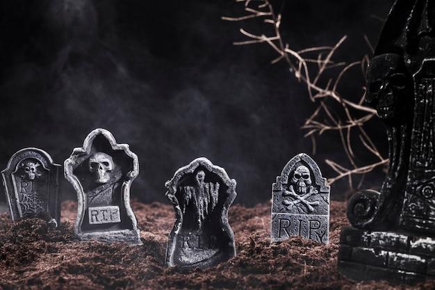 Lápides e galhos no cemitério à noite Foto gratuita