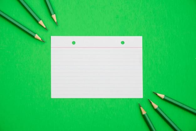 Lápis afiados e papel de linha texturizado sobre fundo verde brilhante Foto gratuita