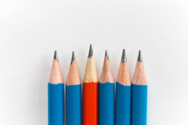 Lápis afiados simples isolados no fundo branco, vermelhos entre os azuis Foto gratuita