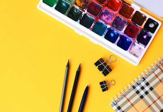 Lápis, caderno, tintas aquarela sobre um fundo amarelo claro. volta ao conceito de escola. Foto Premium