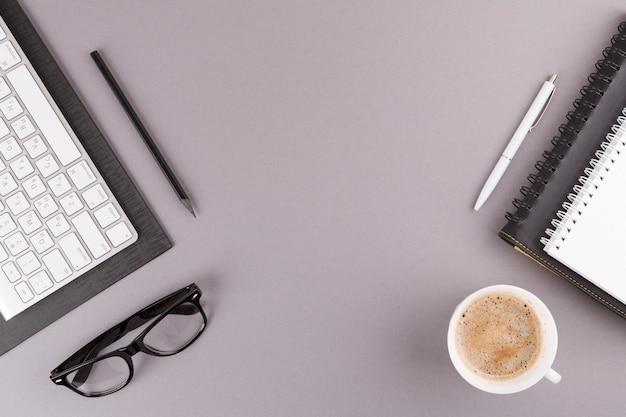 Lápis, caneta e notebooks perto de teclado, óculos e copo Foto gratuita