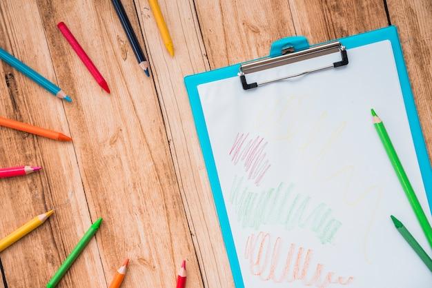 Lápis colorido e prancheta com papel branco na mesa de madeira Foto gratuita