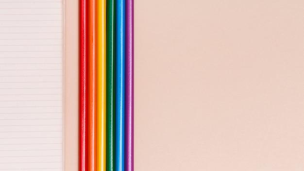 Lápis coloridos de arco-íris e notebook em fundo bege Foto gratuita