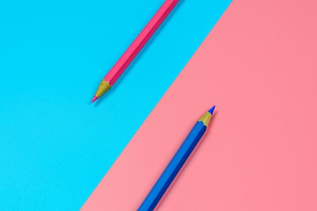 Lápis de cor-de-rosa e azul sobre fundo azul e rosa. Foto Premium