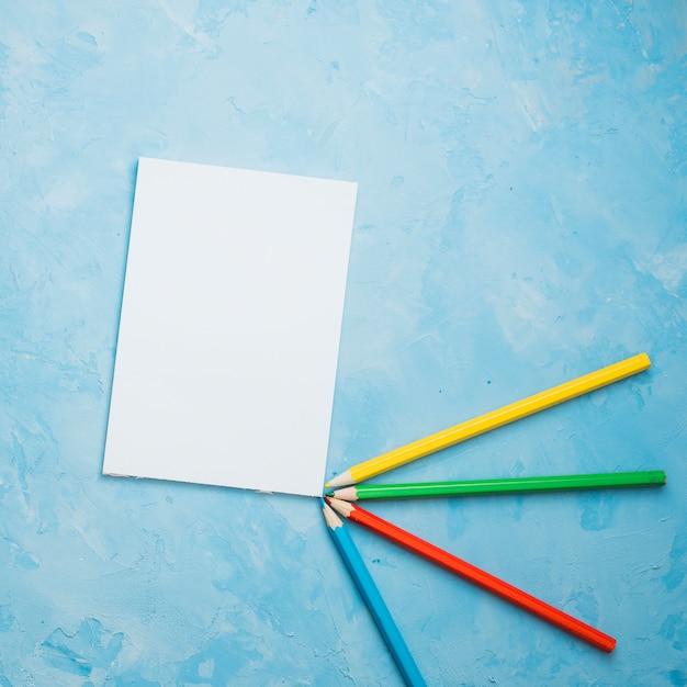 Lápis de cor e folha de papel branco sobre fundo azul Foto gratuita