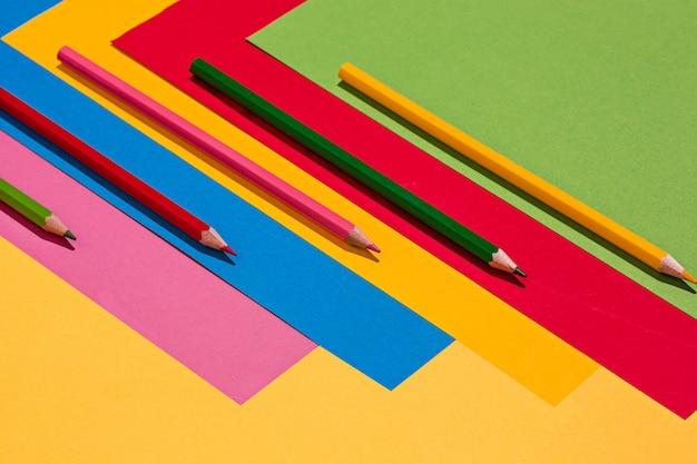 Lápis de cor e folhas de papel colorido Foto gratuita