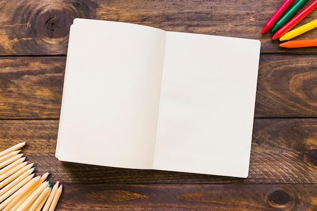 Lápis de cor e lápis perto de caderno aberto Foto gratuita