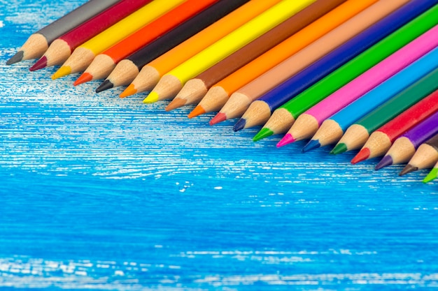 Lápis de cor estão em uma placa azul. Foto Premium