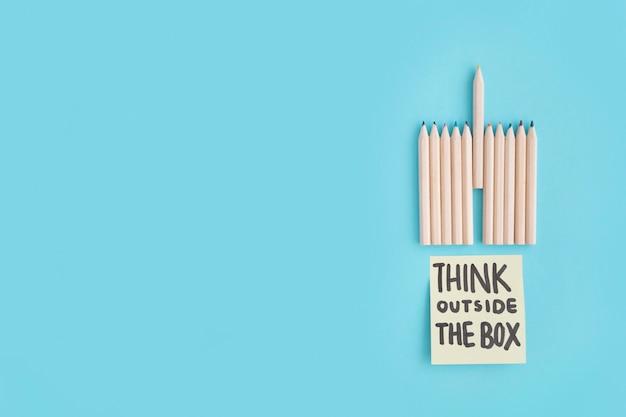 Lápis de cor lápis de cor e pensar fora do texto da caixa na nota sobre o fundo azul Foto gratuita