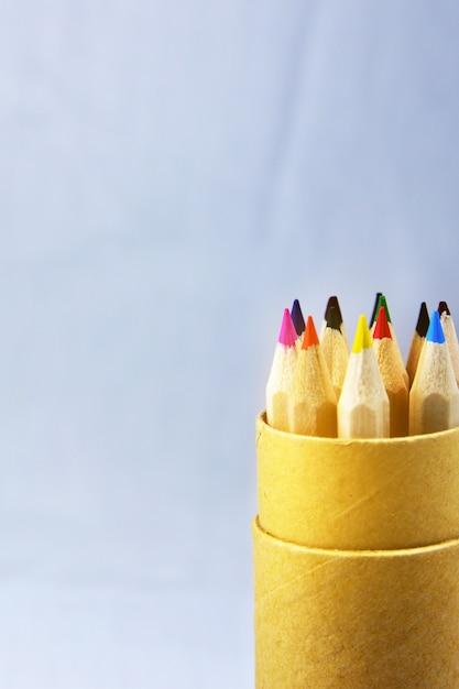Lápis de cor na caixa em fundo azul claro Foto Premium
