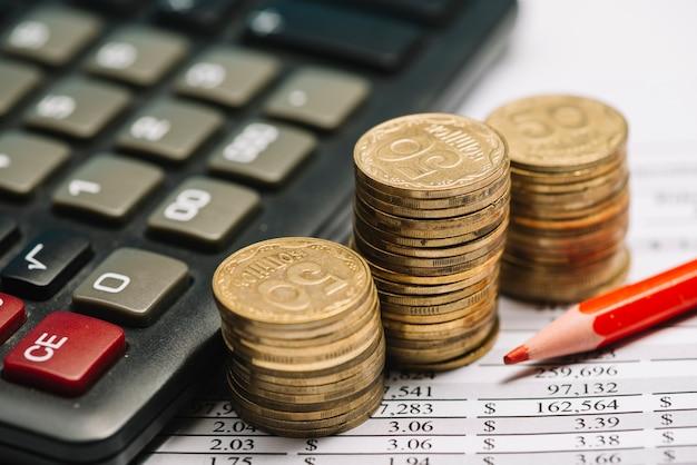 Lápis de cor vermelha com calculadora e pilha de moedas sobre o relatório financeiro Foto gratuita