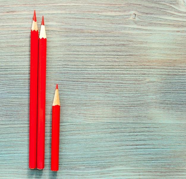 Lápis de cor vermelha, dois longos, um curto, no tampo da mesa de madeira natural azul turquesa. fechar-se. vista do topo. foco seletivo suave. . espaço da cópia do texto. Foto Premium