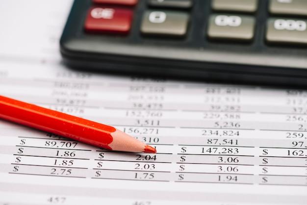 Lápis de cor vermelha e calculadora sobre o relatório financeiro Foto gratuita