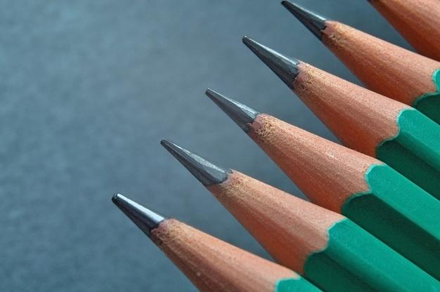 Lápis de madeira afiados verdes com grafite preta sobre fundo escuro texturizado. fechar-se. Foto Premium