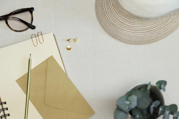 Lápis de ouro, clipes de papel, pinos, ofício envelope no caderno aberto com chapéu Foto Premium