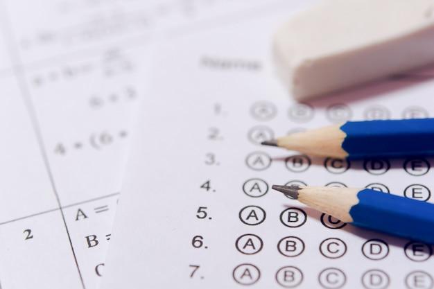Lápis e borracha nas folhas de respostas ou no formulário de teste padronizado com as respostas borbulhadas. folha de respostas de múltipla escolha Foto Premium