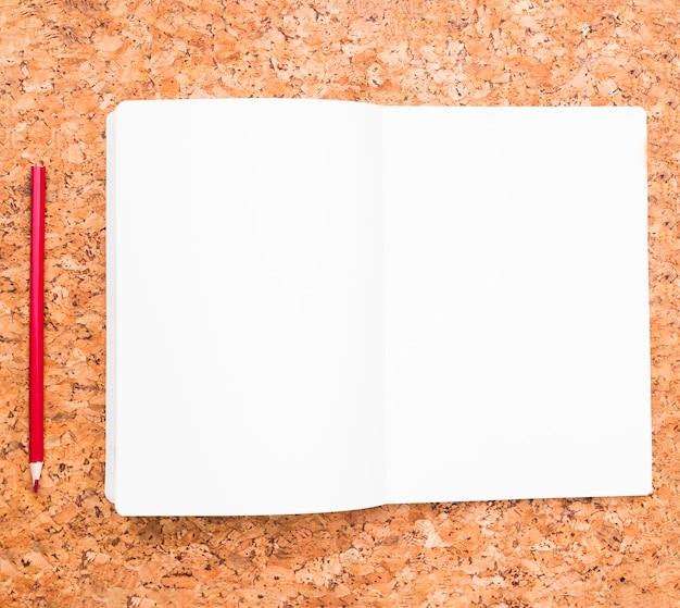 Lápis e caderno aberto Foto gratuita