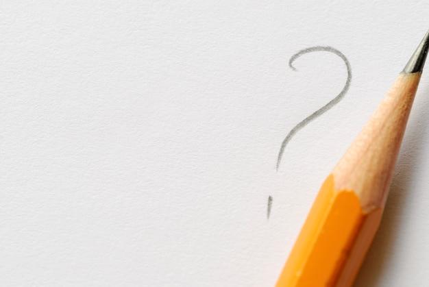 Lápis junto ao ponto de interrogação em papel branco Foto Premium