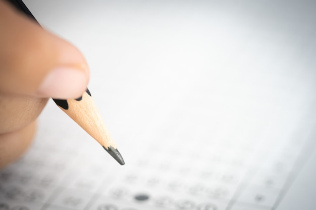 Lápis na mão escrevendo resposta do exame de teste de pergunta no papel de resposta Foto Premium