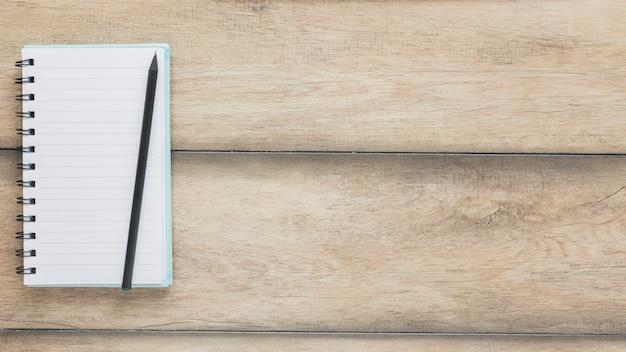Lápis no caderno aberto na mesa de madeira Foto gratuita