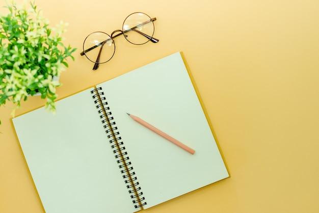 Lápis, óculos e bloco de notas em um fundo abstrato bege Foto Premium