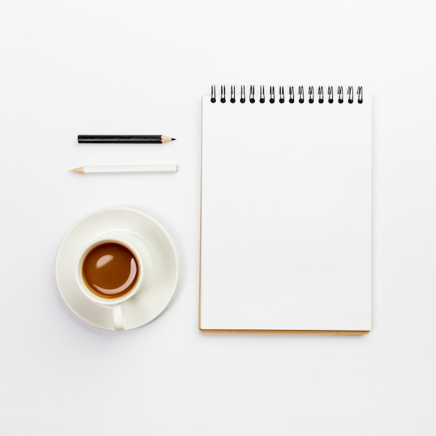 Lápis preto e branco com xícara de café e o bloco de notas em branco em espiral na mesa de escritório Foto gratuita