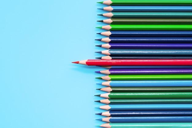 Lápis vermelho que está para fora no fundo azul. liderança, exclusividade Foto Premium