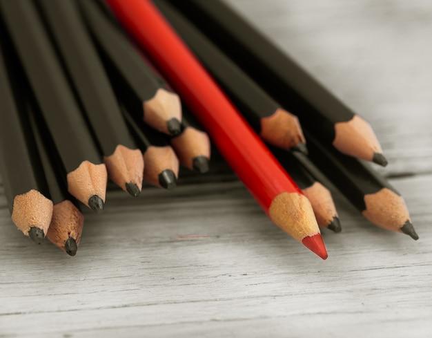 Lápis vermelho se destaca na multidão de lápis preto sobre fundo branco de madeira. Foto gratuita