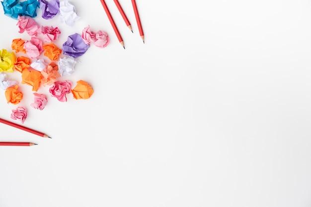 Lápis vermelhos e papel amassado colorido sobre a superfície branca Foto gratuita