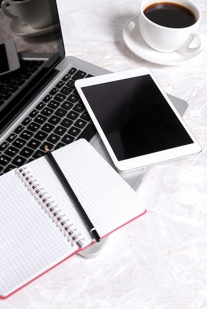Laptop, bloco de notas e caneta em cima da mesa com uma xícara de café e com outros dispositivos Foto gratuita