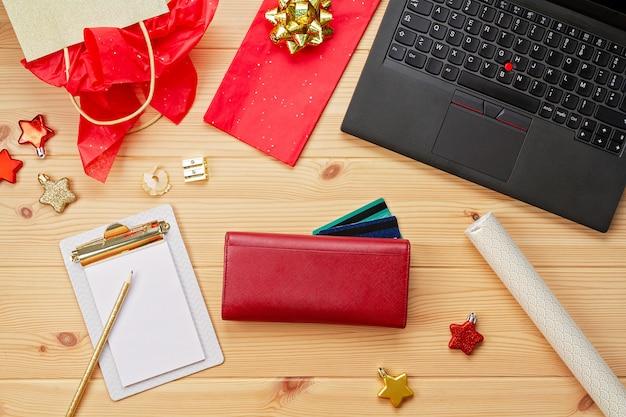 Laptop, cartões de crédito, bolsa e decoração de natal. compras de natal online, compra de presentes Foto Premium
