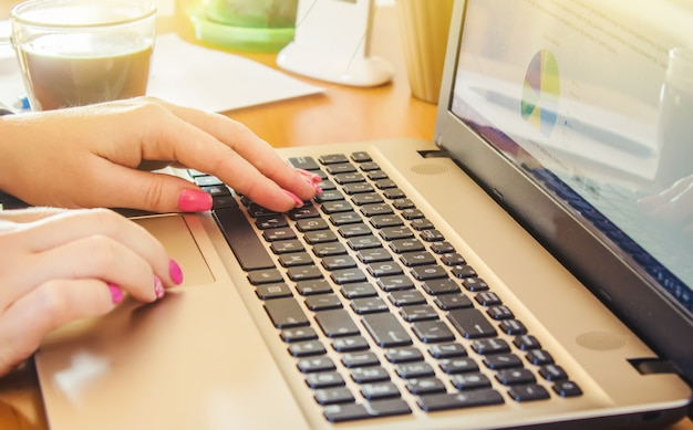 Laptop close-up de um teclado e uma xícara de café quente de manhã. foco seletivo. Foto Premium