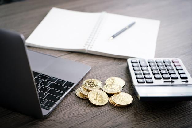 Laptop com calculadora e bitcoin dourado. conceito de investidores de criptomoeda. Foto Premium