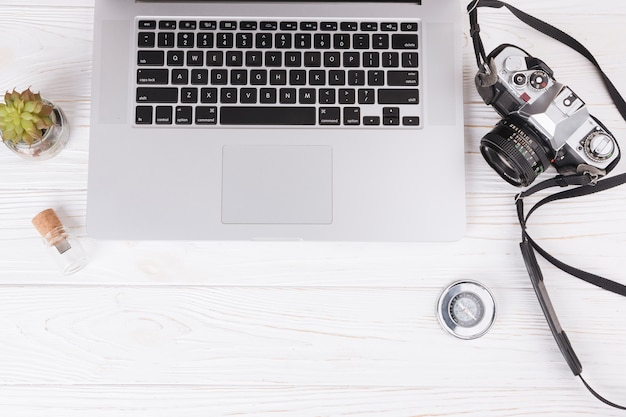 Laptop com câmera e bússola na mesa Foto gratuita