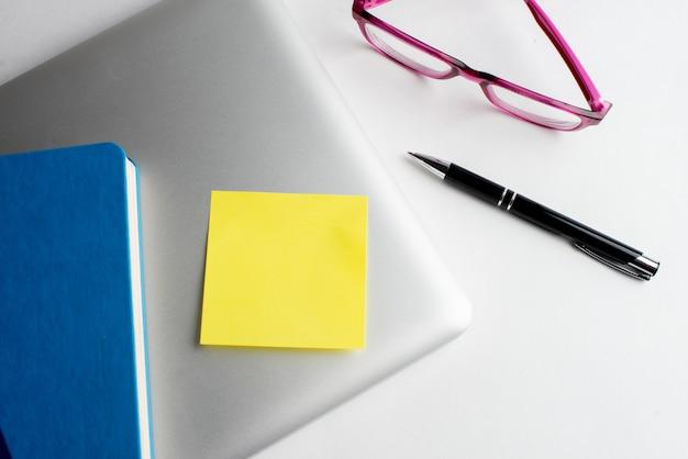 Laptop com caneta de nota amarela e óculos e caneta preta Foto Premium