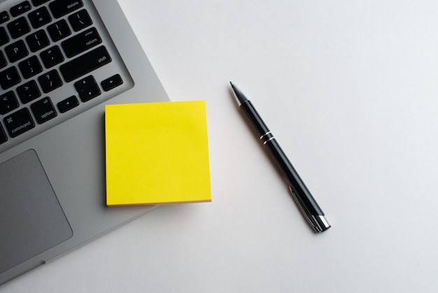 Laptop com caneta preta com blocos amarelos na mesa Foto Premium