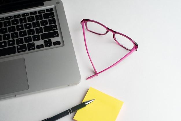 Laptop com caneta preta e blocos coloridos, óculos na mesa Foto Premium