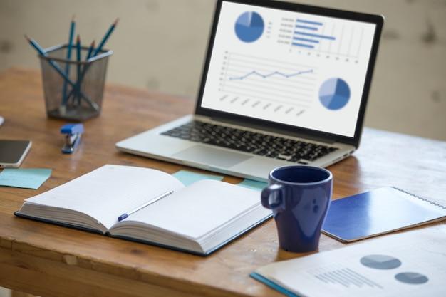 Laptop com gráficos em uma mesa Foto Premium