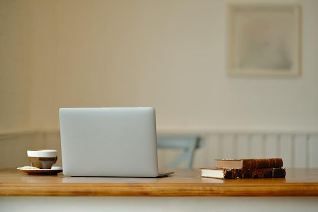 Laptop com material de escritório e gadgets na mesa de madeira Foto Premium