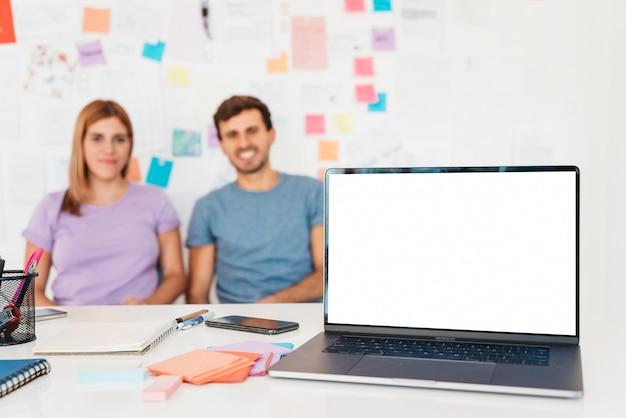Laptop com papelaria contra o fundo do casal e parede com notas Foto gratuita