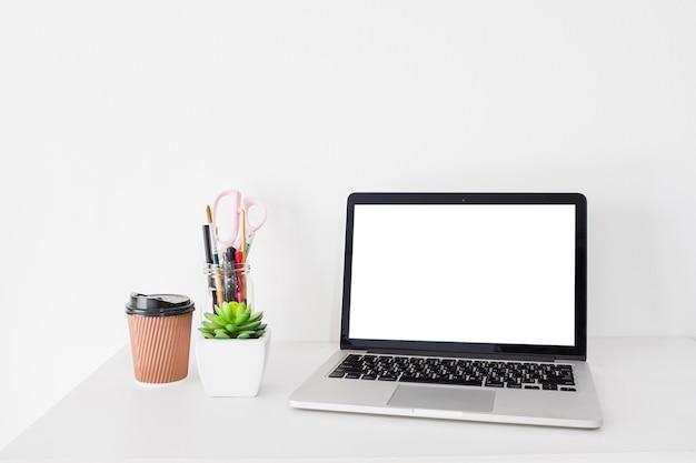 Laptop com tela branca em branco e copo de eliminação na mesa Foto gratuita